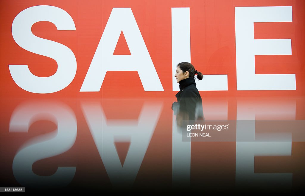 A picture taken using a pre-positioned reflective surface to produce the reflection shows a woman passing a sign advertising an in-store sale in central London on December 16, 2012, less than two weeks before Christmas. AFP PHOTO / LEON NEAL