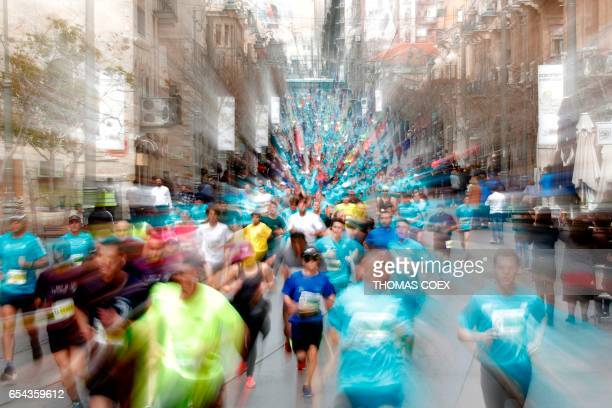 A picture taken using a zoom effect shows competitors running during Jerusalem's 7th marathon on March 17 2017 / AFP PHOTO / THOMAS COEX