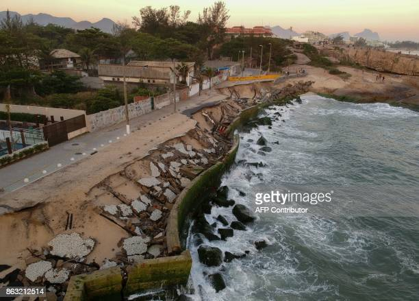 A picture taken with a drone on October 19 2017 shows a collapsed boardwalk destroyed by waves at Macumba beach in Rio de Janeiro Brazil According to...