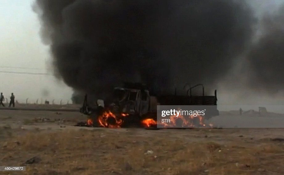 A picture taken with a mobile phone shows a vehicle ablaze on a road in Hawijah, west of Kirkuk, in northern Iraq on June 11, 2014. Jihadists seized all of Mosul and Nineveh province, long a militant stronghold and one of the most dangerous areas in the country, and also took areas in Kirkuk province, to its east, and Salaheddin to the south.