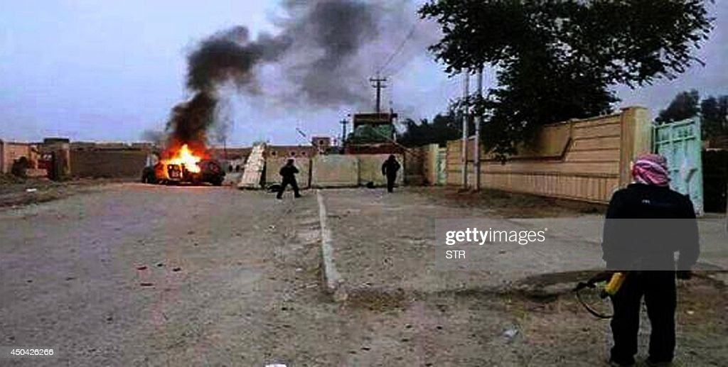 A picture taken with a mobile phone shows an armed man watching as a vehicle, reportedly belonging to Iraqi security forces, is seen in flames on June 10, 2014 in Mosul, some 370 kms north from the Iraqi capital Baghdad. Some 500,000 Iraqis have fled their homes in Iraq's second city Mosul after Jihadist militants took control, fearing increased violence, the International Organization for Migration said.