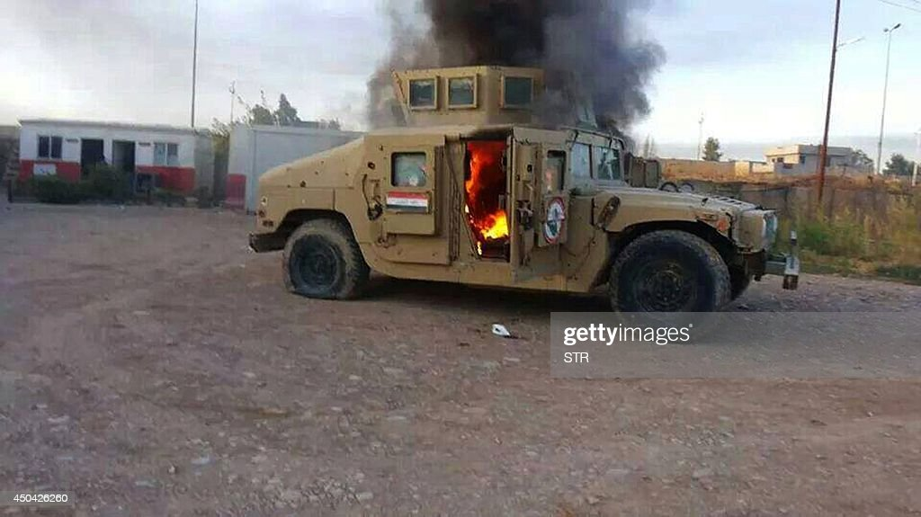 A picture taken with a mobile phone shows an armoured vehicle belonging to Iraqi security forces in flames on June 10, 2014, after hundreds of militants from the Islamic State of Iraq and the Levant (ISIL) launched a major assault on the security forces in Mosul, some 370 kms north from the Iraqi capital Baghdad. Some 500,000 Iraqis have fled their homes in Iraq's second city Mosul after Jihadist militants took control, fearing increased violence, the International Organization for Migration said.