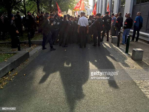 A picture taken with a mobile phone shows French police officers pushing back demonstrators who protest outside a nursery school prior to the arrival...