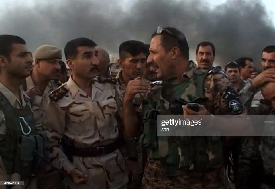 A picture taken with a mobile phone shows Iraqi soldiers talking as smoke billows behind them on a road in Hawijah, west of Kirkuk, in northern Iraq on June 11, 2014. Jihadists seized all of Mosul and Nineveh province, long a militant stronghold and one of the most dangerous areas in the country, and also took areas in Kirkuk province, to its east, and Salaheddin to the south.