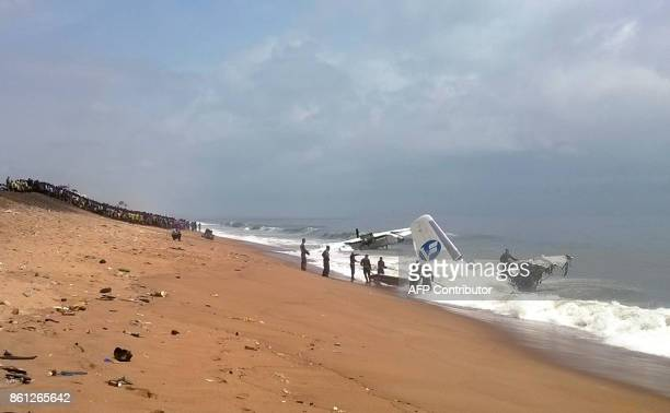 A picture taken with a mobile phone shows members of rescue services standing on the beach of PortBouet in Abidjan as they look at the wreckage of a...