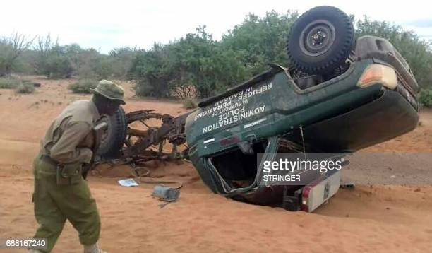 TOPSHOT A picture taken with a mobile photo on May 25 2017 shows a policeman looking at the wreckage of a police vehicle following a road side bomb...