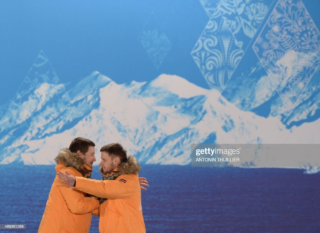 A picture taken with a robotic camera shows Latvia's bronze medalists Andris Sics (L) and Juris Sics celebrating during the Luge Doubles Medal Ceremony at the Sochi medals plaza during the Sochi Winter Olympics on February 14, 2014.
