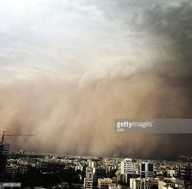 A picture taken with a smartphone shows a sandstorm engulfing the Iranian capital Tehran on June 02 2014 A massive sandstorm and record winds killed...