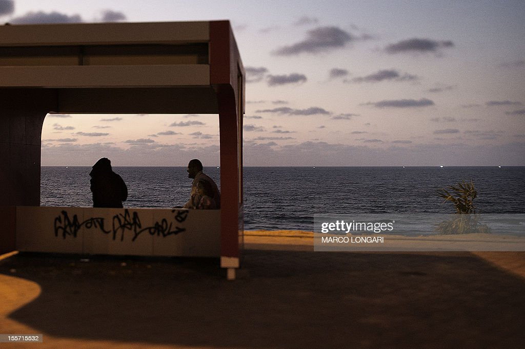 A picture taken with a tilt and shift lens shows a Palestinian family sitting on a bench at a seaside promenade as the sun sets in Gaza City on November 7, 2012. AFP PHOTO/MARCO LONGARI