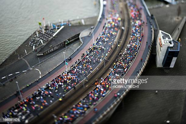 A picture taken with a tiltshift lens shows runners crossing the Erasmus Bridge in Rotterdam during the Rotterdam Marathon on April 14 2013 OUT