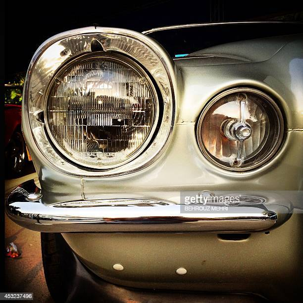 A picture taken with an Hipstamatic application shows the headlight of a 1970 American Chevrolet Camaro SS during a classic cars show at Saadabad...