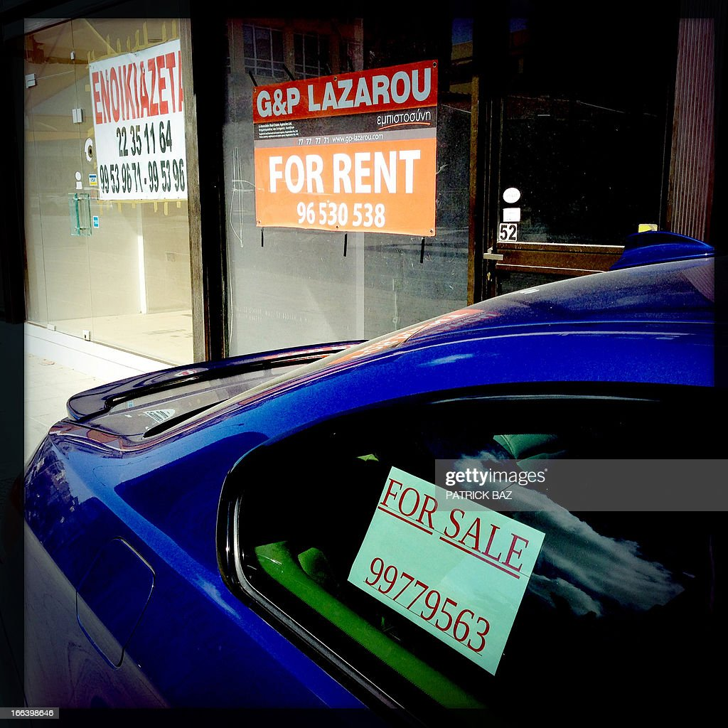 A picture taken with an iPhone using Hipstamatic shows a car with a 'For Sale' sign parked next to a shop with a 'For Rent' sign displayed on its window, in the Cypriot capital Nicosia on March 30, 2013. AFP PHOTO/PATRICK BAZ