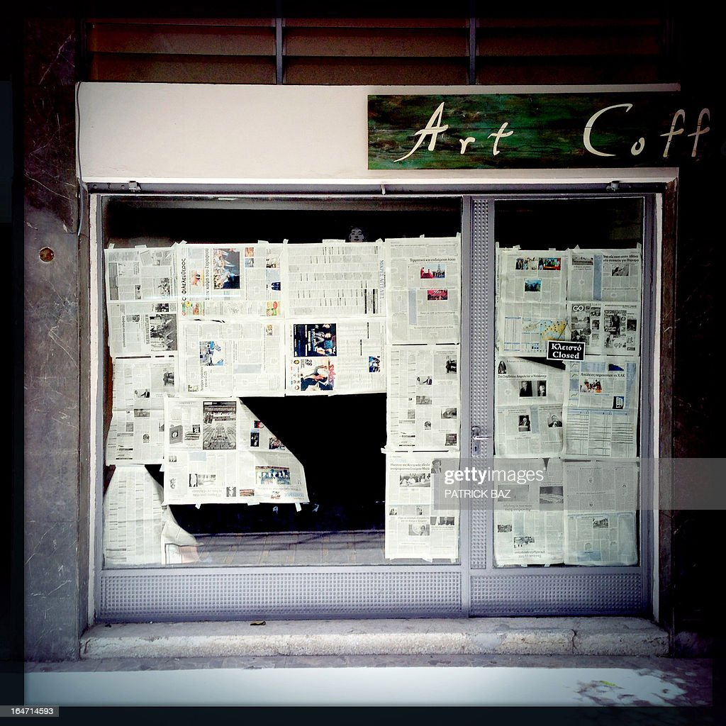 A picture taken with an iPhone using Hipstamatic shows a closed shop with its windows plastered with newspapers in the Cypriot capital, Nicosia, on March 27, 2013. AFP PHOTO/PATRICK BAZ