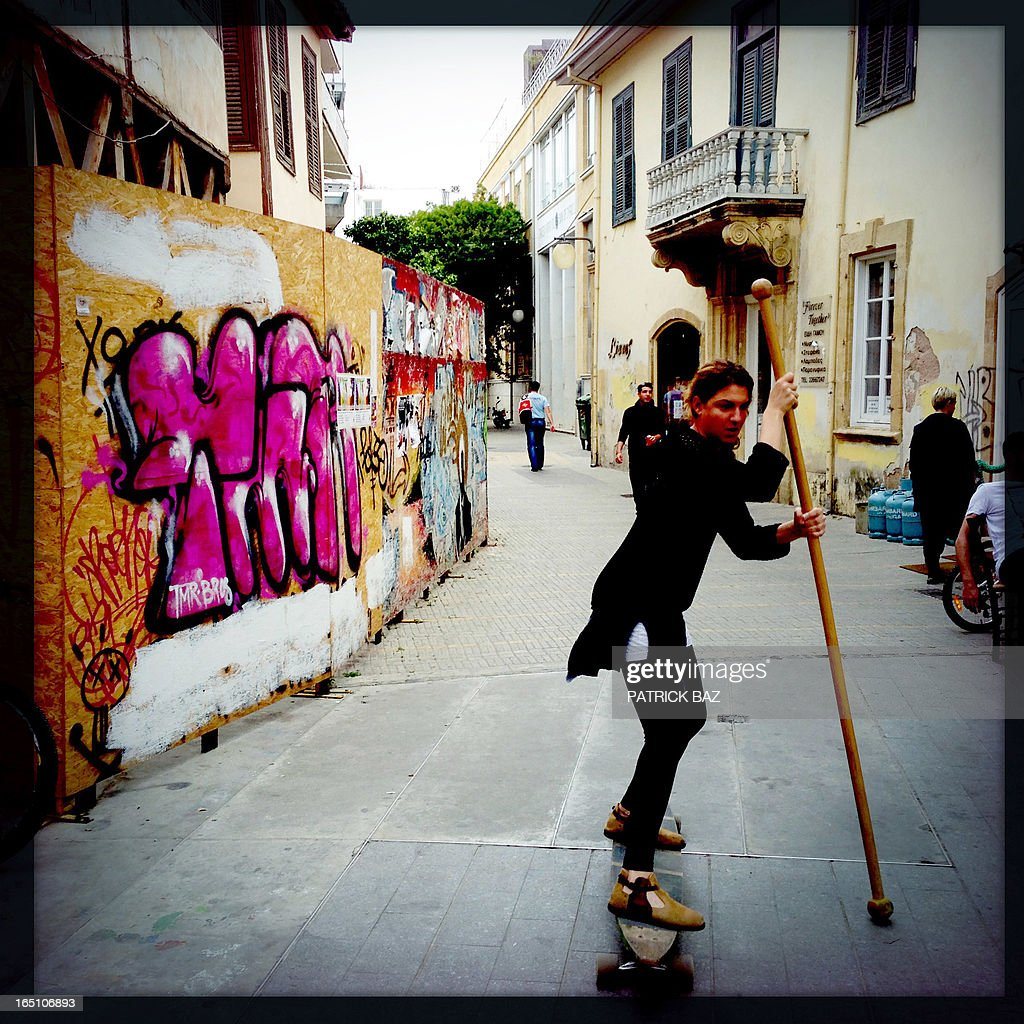 A picture taken with an iPhone using Hipstamatic shows a Cypriot playing with a skateboard in the old part of Nicosia on March 30, 2013. Big savers in Cyprus's largest bank face losses of up to 60 percent, far greater than originally feared under the island's controversial EU-led bailout plan, officials said on March 30. AFP PHOTO/PATRICK BAZ