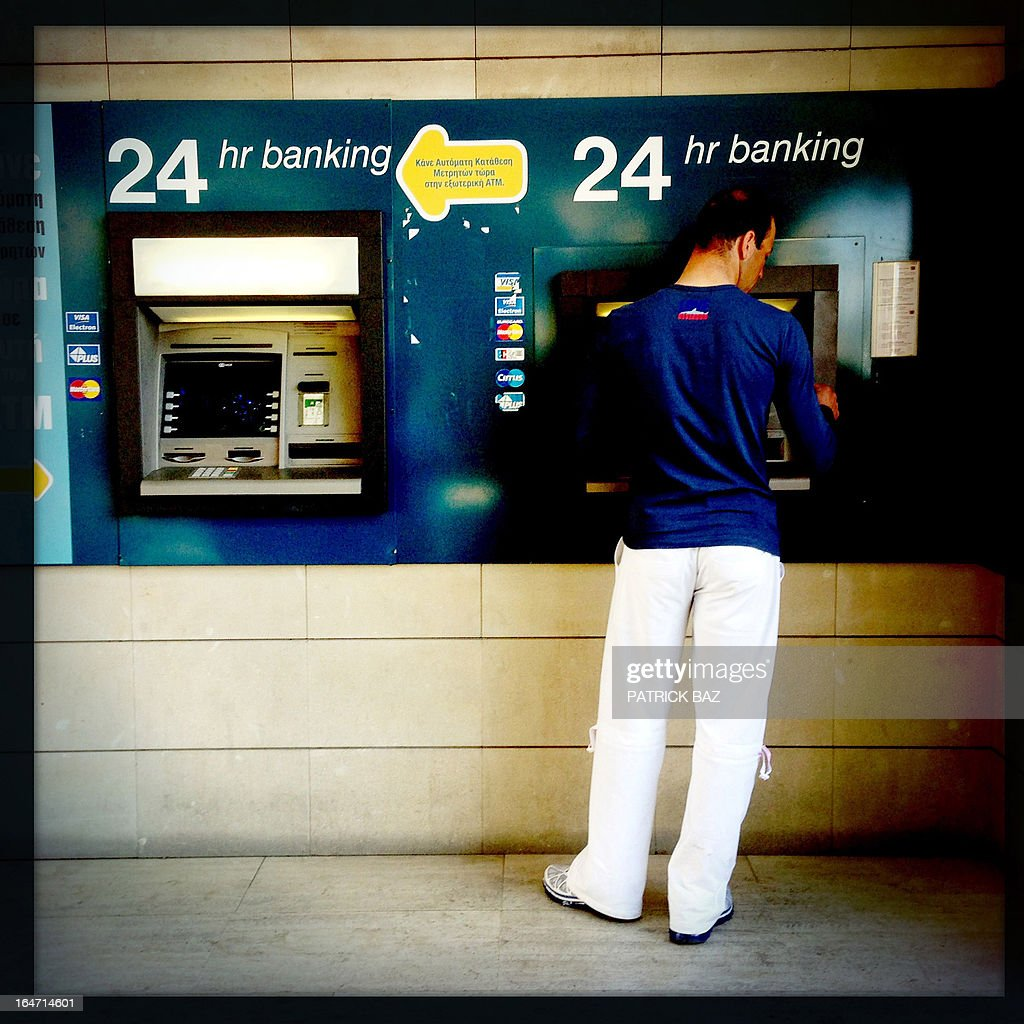A picture taken with an iPhone using Hipstamatic shows a man withdrawing money from an ATM machine in the Cypriot capital, Nicosia, on March 27, 2013.