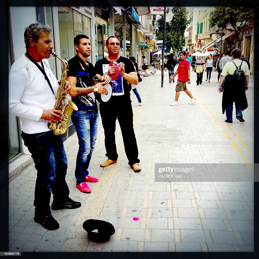 A picture taken with an iPhone using Hipstamatic shows a street music group in the old part of the Cypriot capital, Nicosia, on March 29, 2013.
