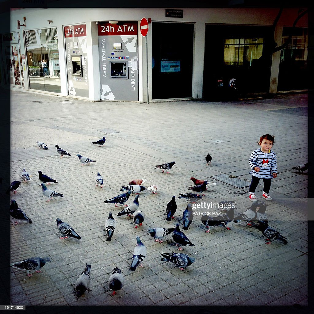 A picture taken with an iPhone using Hipstamatic shows a young girl feeding pigeons a closed shop in the old part of the Cypriot capital, Nicosia, on March 27, 2013.