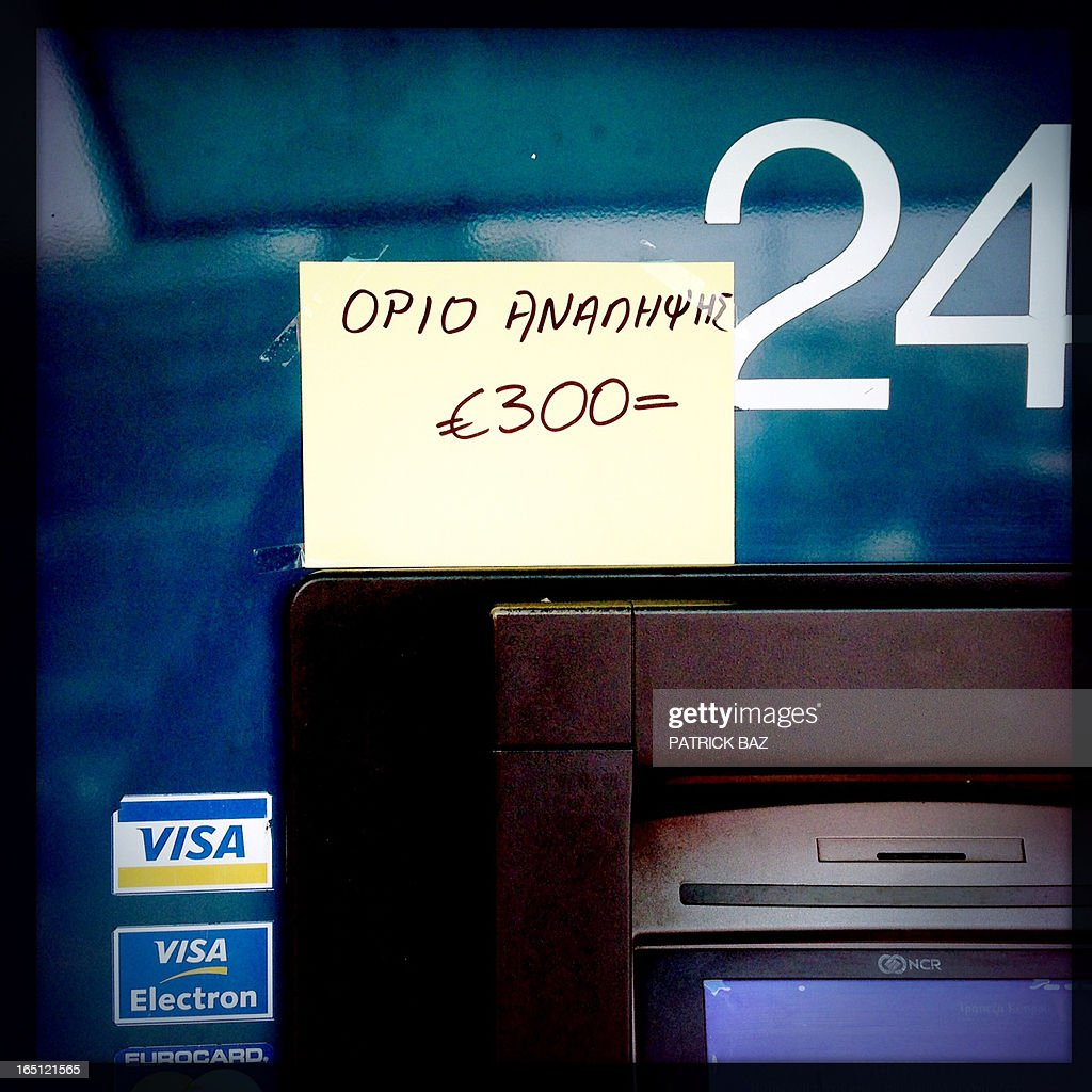 A picture taken with an iPhone using Hipstamatic shows an Bank of Cyprus ATM maching with a note posted on it which reads in Greek 'withdrawal limit 300 €' in the Cypriot port city of Limassol on March 31, 2013.