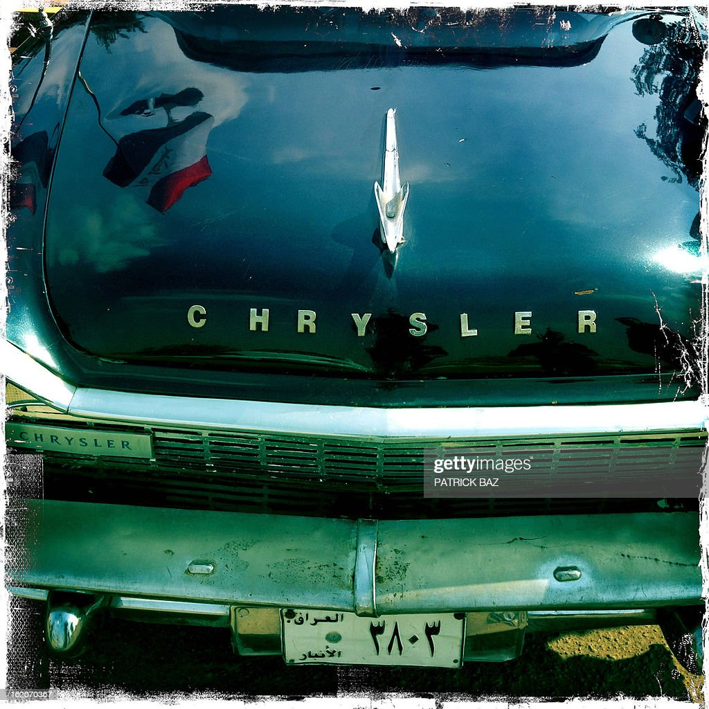 A picture taken with an iPhone using Hipstamatic shows an Iraqi flag refected on a 1958 Chrysler during the Friday motor show in Baghdad's district of Al-Jadriya on February 8, 2013.