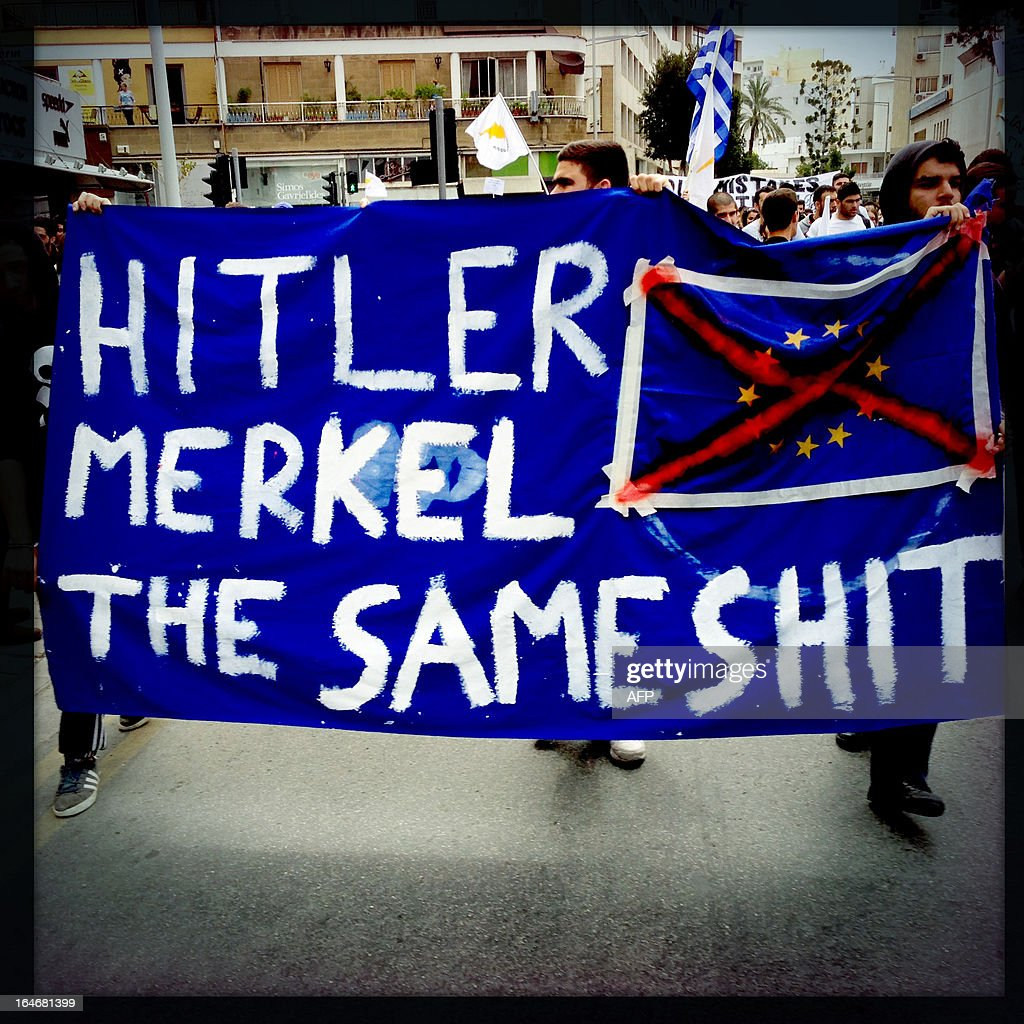 A picture taken with an iPhone using Hipstamatic shows Cypriot college students holding a banner comparing German Chancellor Angela Merkel to Nazi dictator Adolf Hitler during a protest in Nicosia against a bailout for the financially crippled island on March 26, 2013. AFP PHOTO/PATRICK BAZ