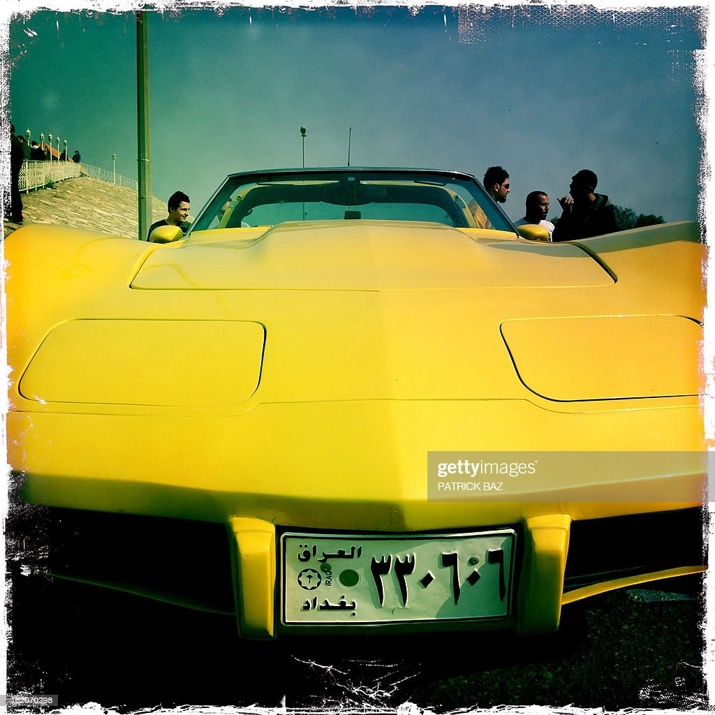 A picture taken with an iPhone using Hipstamatic shows Iraqi youth standing next to a Chevrolet Corvette from the 1970s during the Friday motor show in Baghdad's district of Al-Jadriya on February 8, 2013. AFP PHOTO / PATRICK BAZ