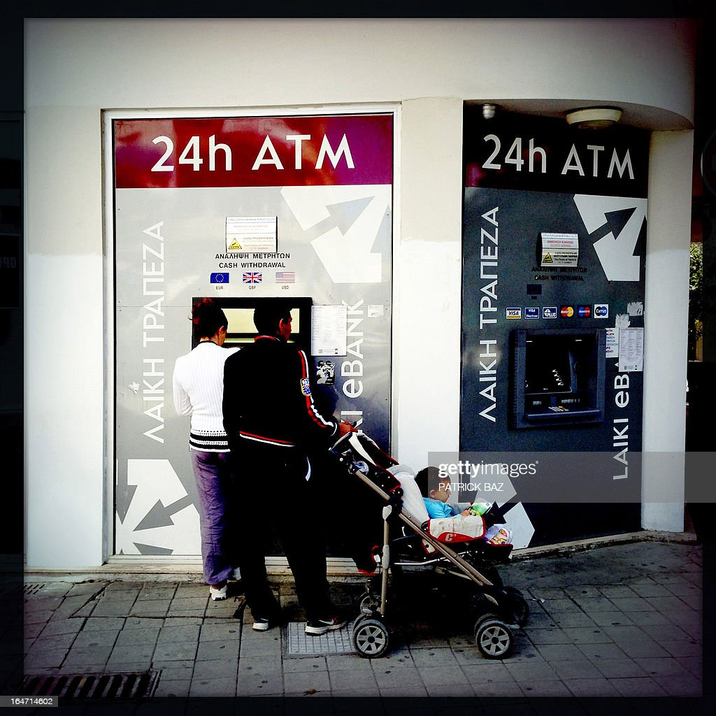 A picture taken with an iPhone using Hipstamatic shows people withdrawing money from an ATM machine in the Cypriot capital, Nicosia, on March 27, 2013. AFP PHOTO/PATRICK BAZ