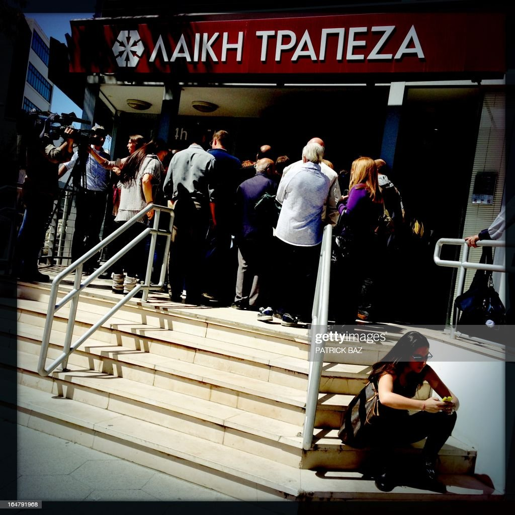A picture taken with an iPhone using Hipstamatic shows people queuing at a branch of the Cyprus Popular Bank, Laiki, in the Cypriot capital, Nicosia, on March 28, 2013. As Cyprus reels under a bailout that painfully pares back its finance sector, many bankers, auditors and accountants are facing unemployment, with some being forced to consider leaving the island for good.