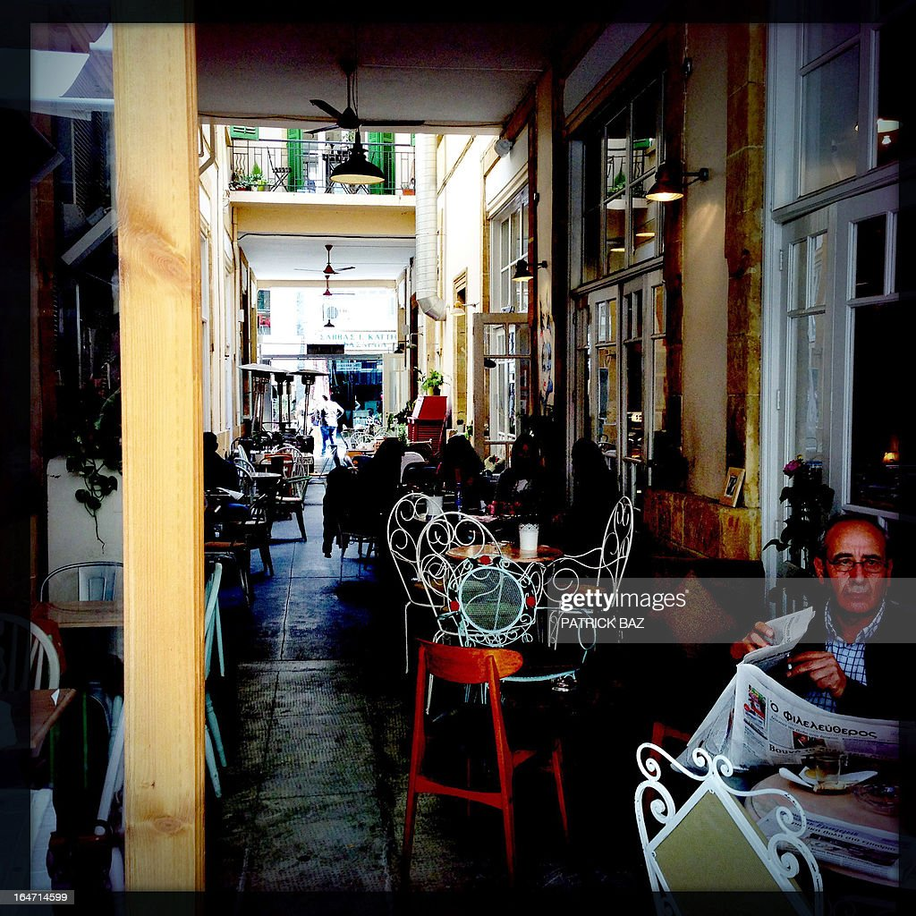 A picture taken with an iPhone using Hipstamatic shows people sitting in a cafe on Ledra Street in the old part of the Cypriot capital, Nicosia, on March 27, 2013. AFP PHOTO/PATRICK BAZ