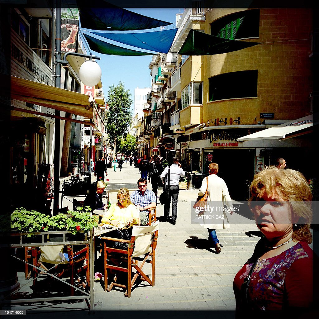 A picture taken with an iPhone using Hipstamatic shows people sitting in a cafe and walking in the centre of the old part of the Cypriot capital, Nicosia, on March 27, 2013.