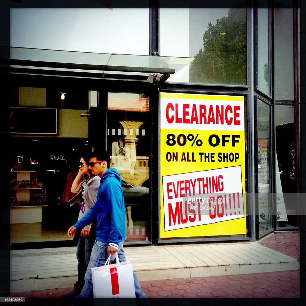 A picture taken with an iPhone using Hipstamatic shows people walking past a shop in the Cypriot capital Nicosia on March 30, 2013.