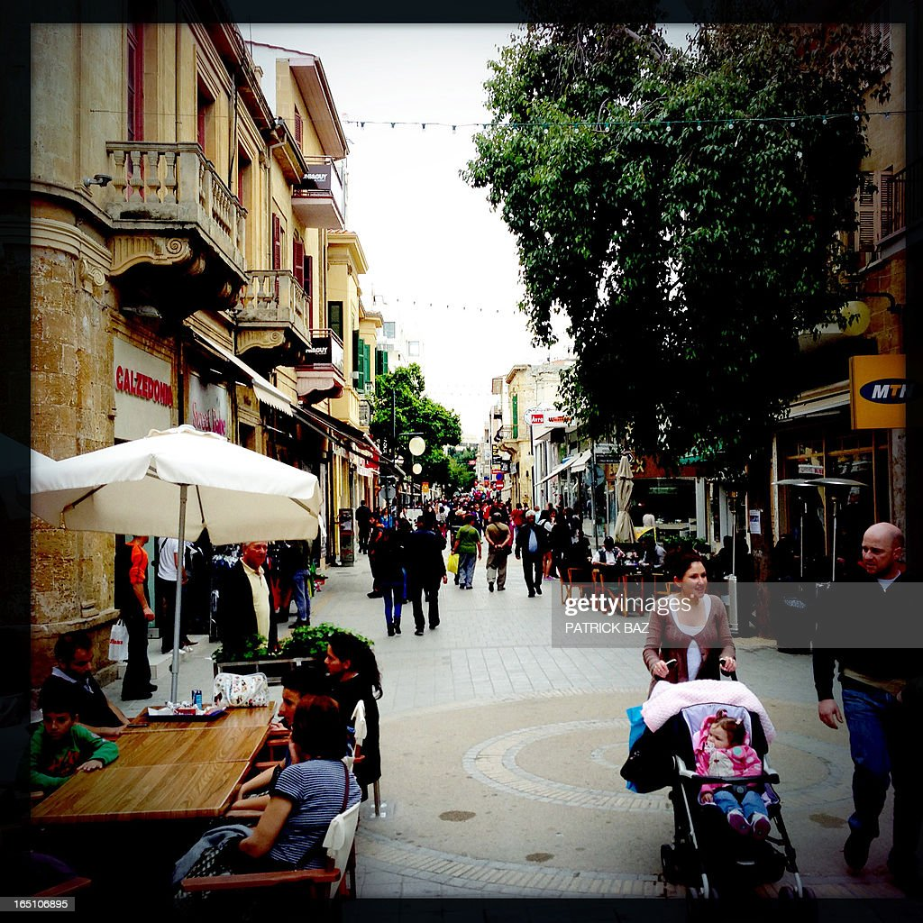 A picture taken with an iPhone using Hipstamatic shows people walking on Ledra street in the old part of Nicosia on March 30, 2013. Big savers in Cyprus's largest bank face losses of up to 60 percent, far greater than originally feared under the island's controversial EU-led bailout plan, officials said on March 30.