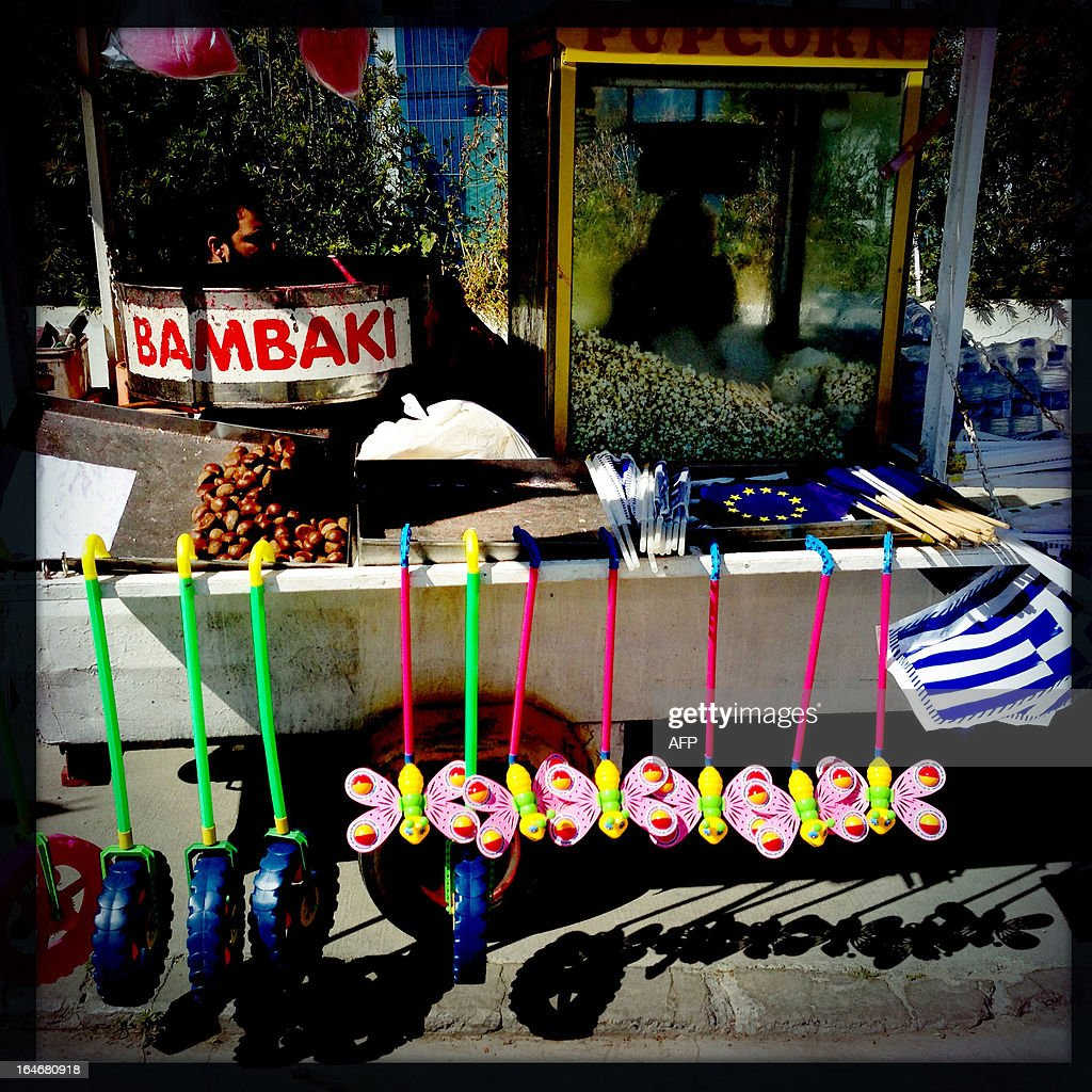 A picture taken with an iPhone using Hipstamatic shows the cart of a street vendor selling EU and Greek flags along with his usual merchandise of snacks and toys in the old city of the Cypriot capital Nicosia on March 25, 2013.
