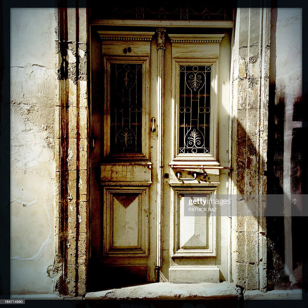 A picture taken with an iPhone using Hipstamatic shows the door of an empty house in the old part of the Cypriot capital, Nicosia, on March 27, 2013. AFP PHOTO/PATRICK BAZ