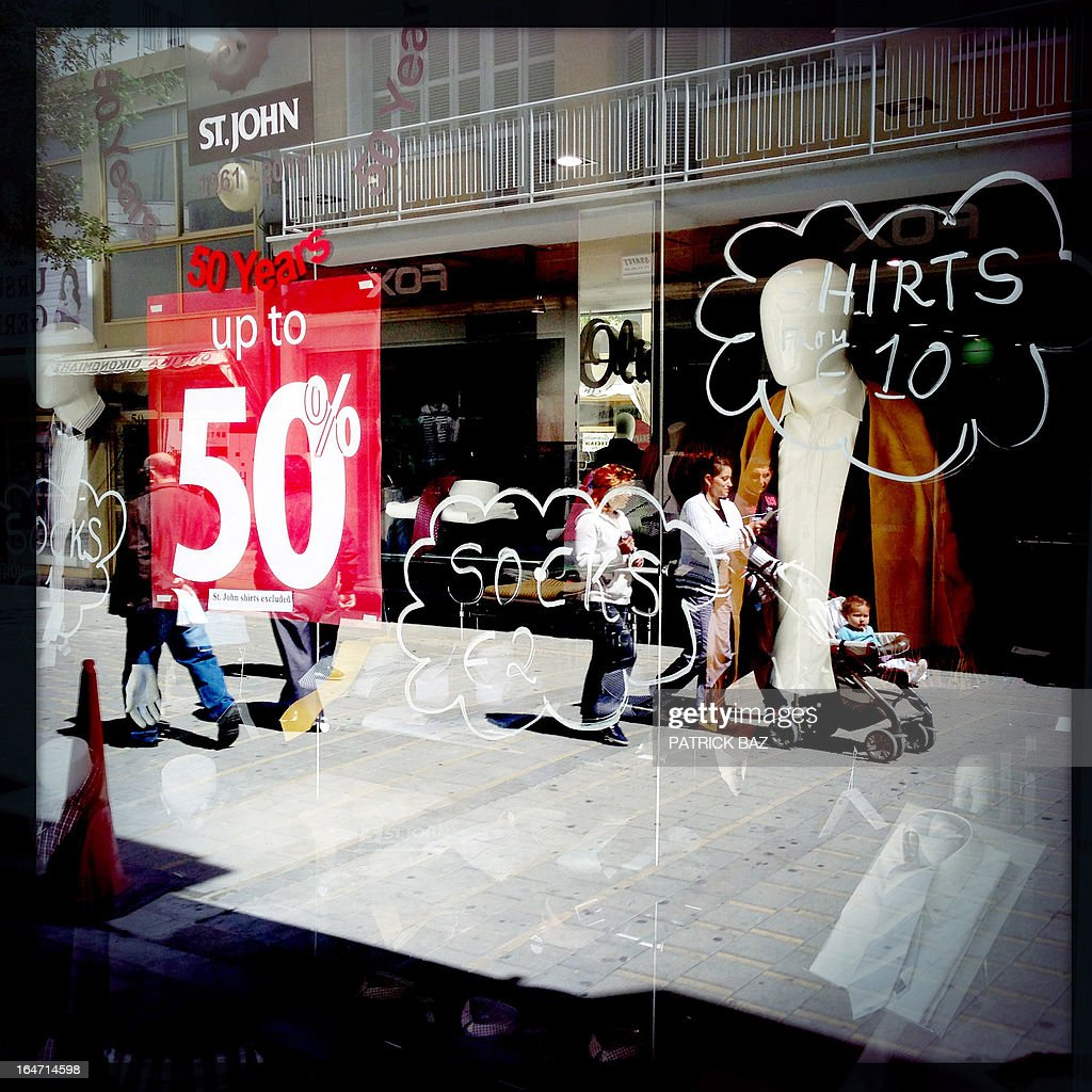 A picture taken with an iPhone using Hipstamatic shows the reflection of people shopping on Ledra street in the centre of the old part of the Cypriot capital, Nicosia, in a shop window on March 27, 2013.