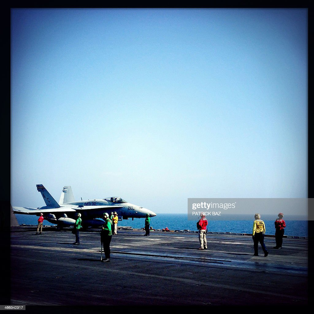 A picture taken with the Hipstamatic application shows a F18 US Navy jet fighter preparing to take off from USS Harry S.Trumann (CVN 75) catapult deck in the Gulf of Oman on January 30, 2014.The Charles de Gaulle and the USS Harry S.Trumann (CVN 75) were conducting combined operations dubbed Bois Belleau.