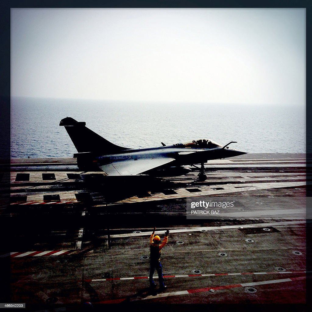 A picture taken with the Hipstamatic application shows a French Navy Rafale fighter jet landing on the flight deck of the Charles de Gaulle sailing in the Gulf of Oman on January 31, 2014.The Charles de Gaulle and the USS Harry S.Trumann (CVN 75) were conducting combined operations dubbed Bois Belleau. AFP PHOTO / PATRICK BAZ