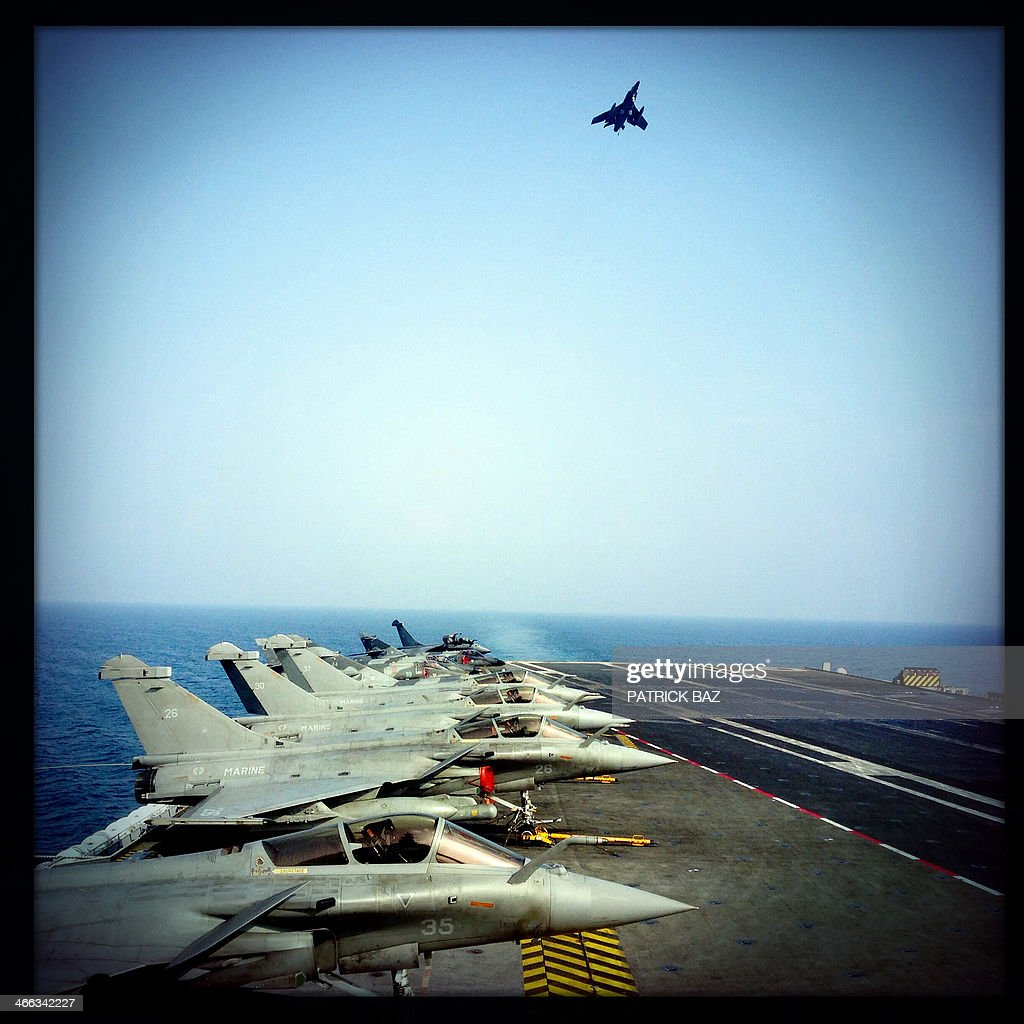 A picture taken with the Hipstamatic application shows a French Navy Super Etendard flying over Rafale fighter jets sat on the flight deck of French aircraft carrier Charles de Gaulle sailing in the Gulf of Oman on January 31, 2014.The Charles de Gaulle and the USS Harry S.Trumann (CVN 75) were conducting combined operations dubbed Bois Belleau. AFP PHOTO / PATRICK BAZ