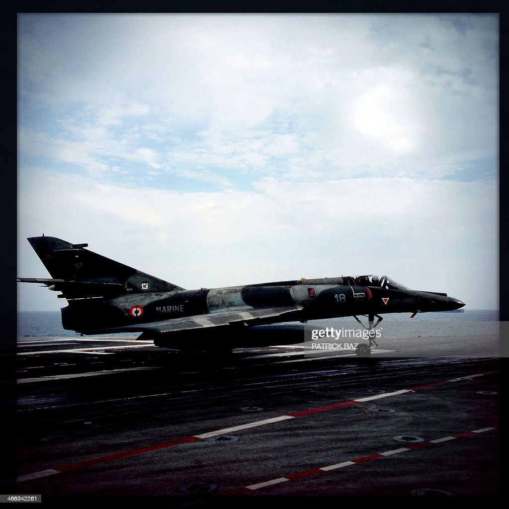 A picture taken with the Hipstamatic application shows a French Navy Super Etendard jet fighter sitting on the flight deck of the aircraft carrier Charles de Gaulle sailing in the Gulf of Oman on January 30, 2014.The Charles de Gaulle and the USS Harry S.Trumann (CVN 75) were conducting combined operations dubbed Bois Belleau.