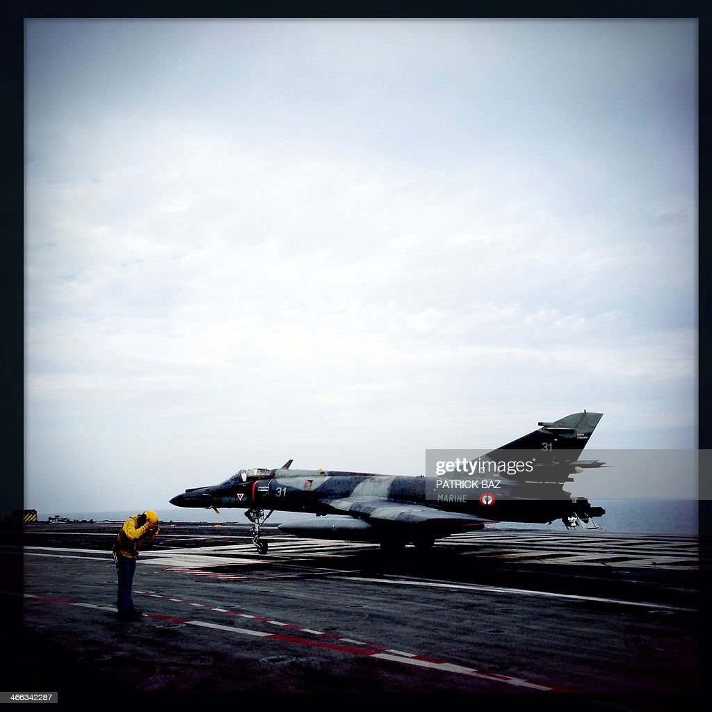 A picture taken with the Hipstamatic application shows a French Navy personnel gesturing to the pilot of a Super Etendard after it landed on the flight deck of the aircraft carrier Charles de Gaulle sailing in the Gulf of Oman on January 30, 2014.The Charles de Gaulle and the USS Harry S.Trumann (CVN 75) were conducting combined operations dubbed Bois Belleau.