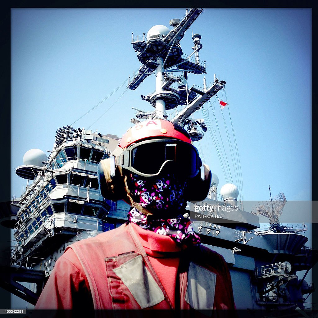 A picture taken with the Hipstamatic application shows a US Navy sailor with his face covered by a scarf decorated with skulls and bones as he works on the flight deck of the USS Harry S.Trumann (CVN 75) in the Gulf of Oman on January 30, 2014.The Charles de Gaulle and the USS Harry S.Trumann (CVN 75) were conducting combined operations dubbed Bois Belleau.