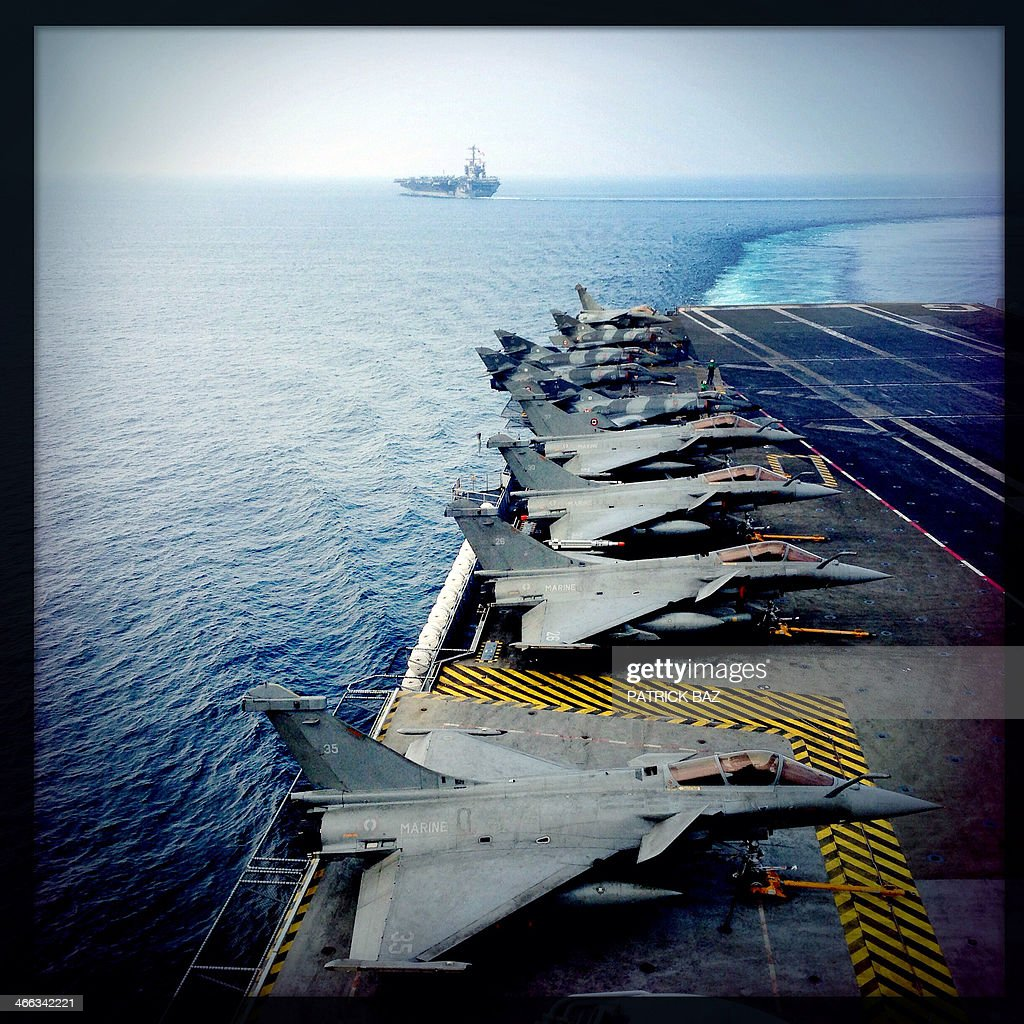 A picture taken with the Hipstamatic application shows French Navy Rafale (foreground) and Super Etendard fighter jets sitting on the flight deck of the Charles de Gaulle as the US Navy aircraft carrier USS Harry S.Trumann (CVN 75) is sailing (background) in the Gulf of Oman on January 31, 2014.The Charles de Gaulle and the USS Harry S.Trumann (CVN 75) were conducting combined operations dubbed Bois Belleau. AFP PHOTO / PATRICK BAZ