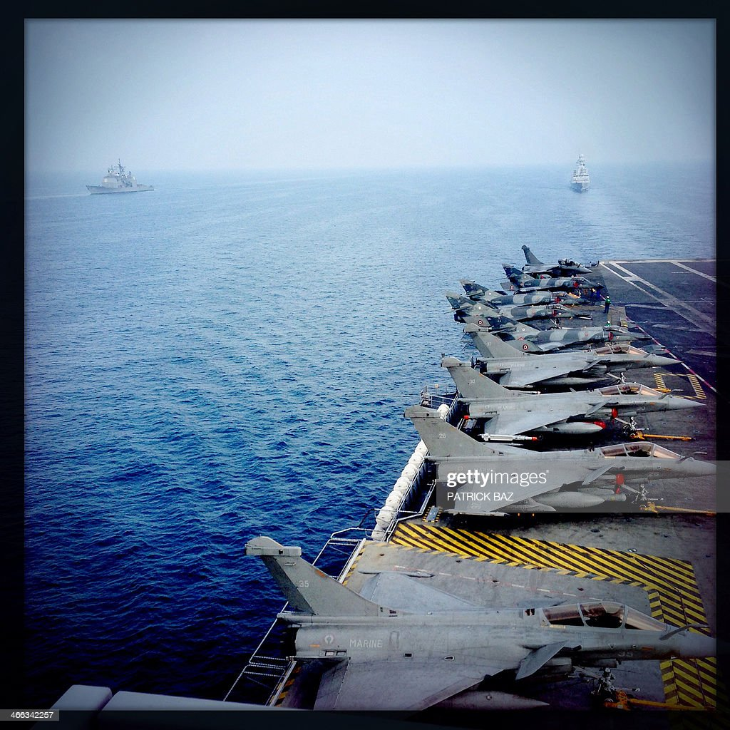 A picture taken with the Hipstamatic application shows French Navy fighter jets Rafale (foreground) and Super Etendards sitting on the flight deck of the aircraft carrier Charles de Gaulle escorted by Navy fregates, French, Forbin (R) and US Gettysburgh while sailing in the Gulf of Oman on January 31, 2014.The Charles de Gaulle and the USS Harry S.Trumann (CVN 75) were conducting combined operations dubbed Bois Belleau.