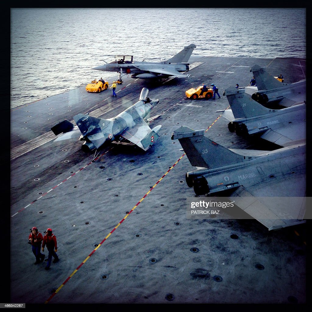 A picture taken with the Hipstamatic application shows French Navy Rafale fighter jets sitting on the flight deck of the aircraft carrier Charles de Gaulle sailing in the Gulf of Oman on January 30, 2014.The Charles de Gaulle and the USS Harry S.Trumann (CVN 75) were conducting combined operations dubbed Bois Belleau.