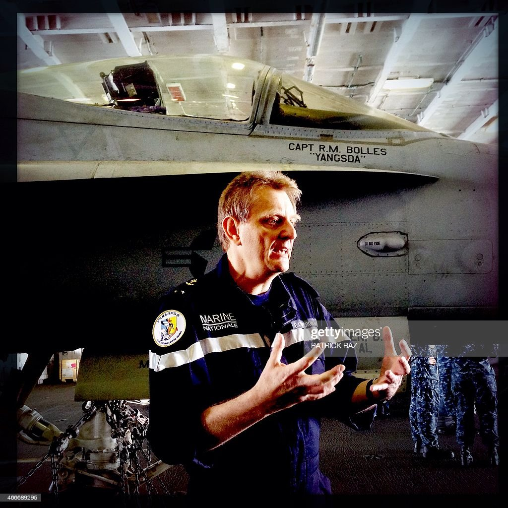 A picture taken with the Hipstamatic application shows French Navy Rear Admiral Eric Chaperon, commander of the French Carrier Strike Group Task Force 473 and the aircraft carrier Charles de Gaulle talking to the media next to an F-18 fighter jet on board the US navy aircraft carrier USS Harry S.Trumann (CVN 75) in the Gulf of Oman on January 30, 2014. The Charles de Gaulle and the USS Harry S.Trumann (CVN 75) were conducting combined operations dubbed Bois Belleau.