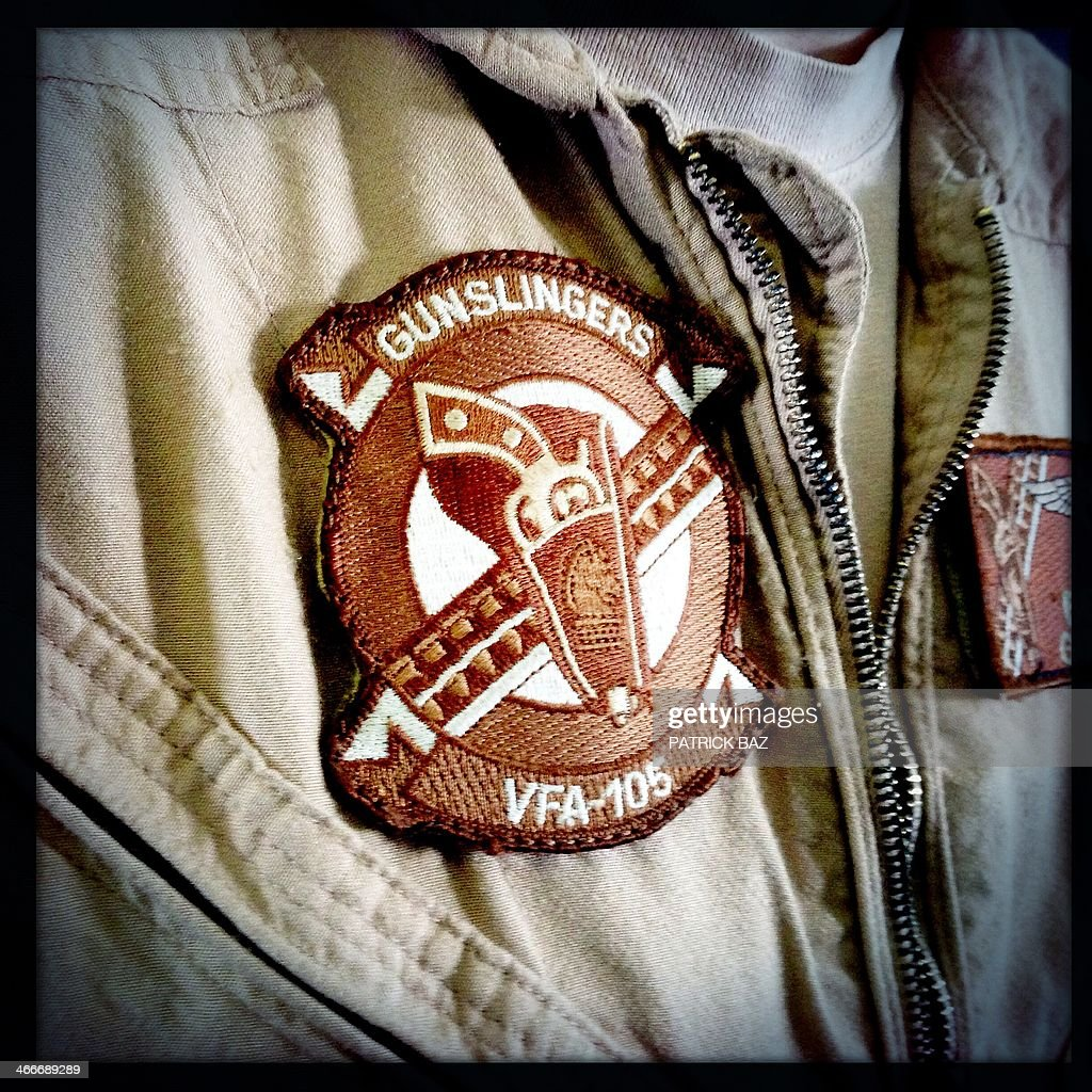 A picture taken with the Hipstamatic application shows the patch of US Navy F-18 jet fighter pilot on the flight deck of the USS Harry S.Trumann (CVN 75) aircraft carrier in the Gulf of Oman on January 30, 2014. The Charles de Gaulle and the USS Harry S.Trumann (CVN 75) were conducting combined operations dubbed Bois Belleau.