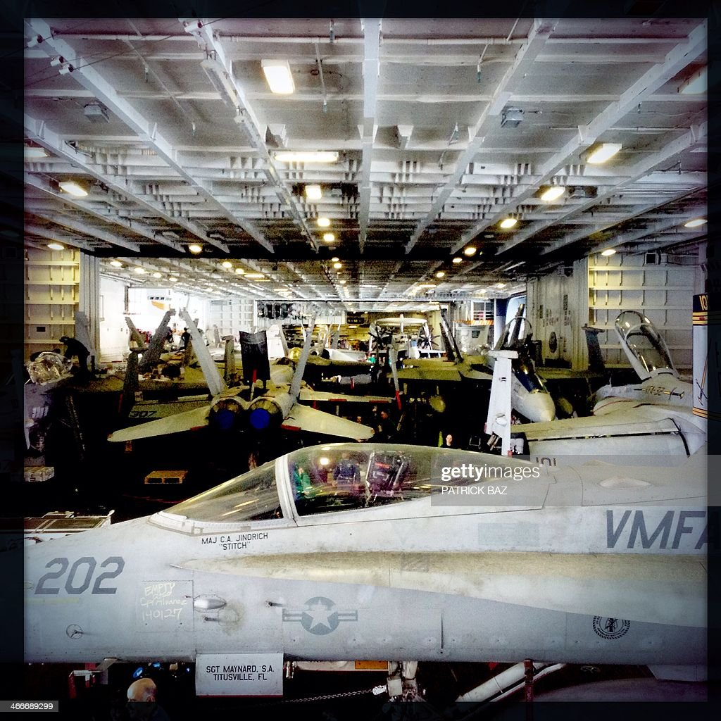 A picture taken with the Hipstamatic application shows US Navy F-18 jet fighters sitting in the hangar of the USS Harry S.Trumann (CVN 75) aircraft carrier in the Gulf of Oman on January 30, 2014. The Charles de Gaulle and the USS Harry S.Trumann (CVN 75) were conducting combined operations dubbed Bois Belleau.