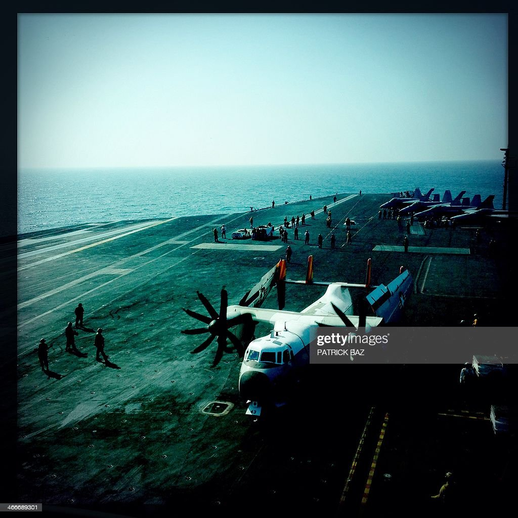 A picture taken with the Hipstamatic application shows US Navy F-18 jet fighters background and a Greyhound transport plane sitting on the flight deck of the USS Harry S.Trumann (CVN 75) aircraft carrier in the Gulf of Oman on January 30, 2014. The Charles de Gaulle and the USS Harry S.Trumann (CVN 75) were conducting combined operations dubbed Bois Belleau. AFP PHOTO / PATRICK BAZ