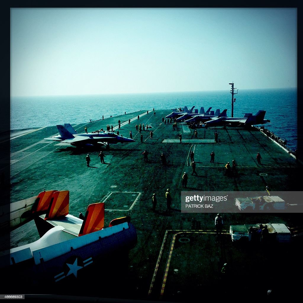 A picture taken with the Hipstamatic application shows US Navy F-18 jet fighters background and a Greyhound transport plane sitting on the flight deck of the USS Harry S.Trumann (CVN 75) aircraft carrier in the Gulf of Oman on January 30, 2014. The Charles de Gaulle and the USS Harry S.Trumann (CVN 75) were conducting combined operations dubbed Bois Belleau.