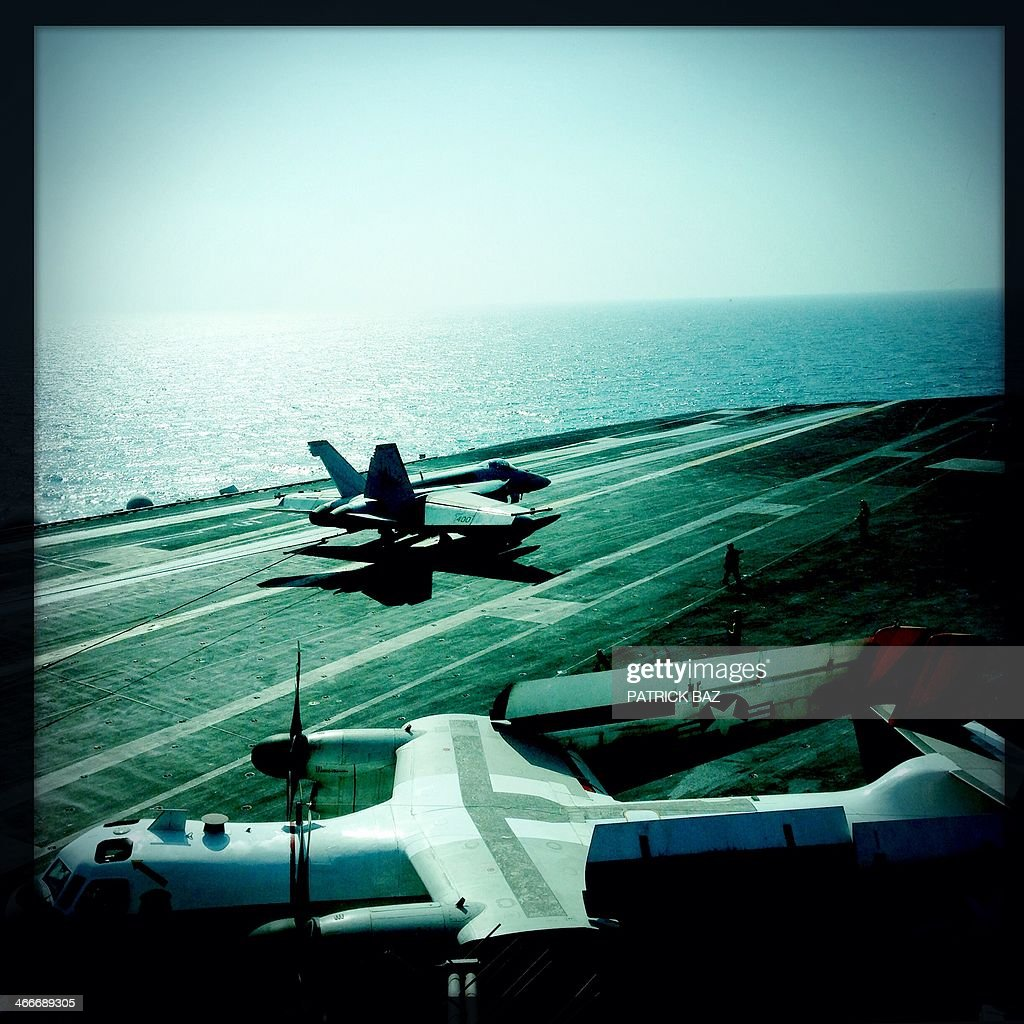 A picture taken with the Hipstamatic application shows US Navy F-18 jet fighter landing next to a Greyhound transport plane on the flight deck of the USS Harry S.Trumann (CVN 75) aircraft carrier in the Gulf of Oman on January 30, 2014. The Charles de Gaulle and the USS Harry S.Trumann (CVN 75) were conducting combined operations dubbed Bois Belleau.