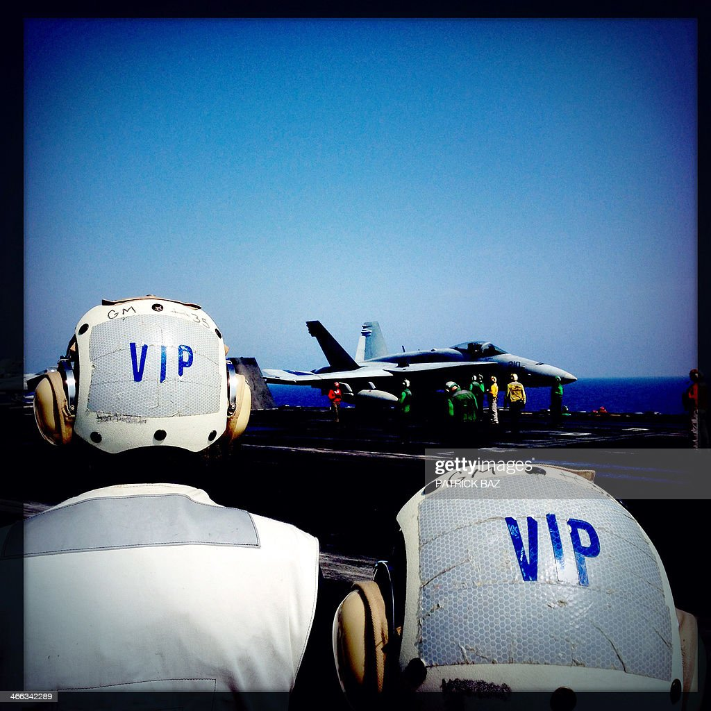 A picture taken with the Hipstamatic application shows VIP guests looking at a F18 US Navy jet fighter preparing to take off from USS Harry S.Trumann (CVN 75) catapult deck in the Gulf of Oman on January 30, 2014.The Charles de Gaulle and the USS Harry S.Trumann (CVN 75) were conducting combined operations dubbed Bois Belleau.